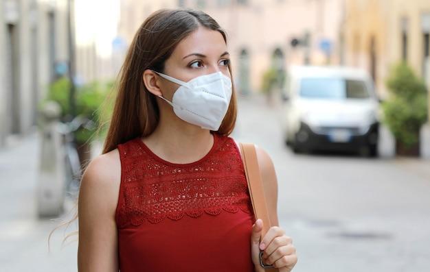 コロナウイルス病2019に対して顔に防護マスクを持つ少女。