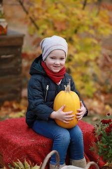 秋の公園でカボチャを持つ少女