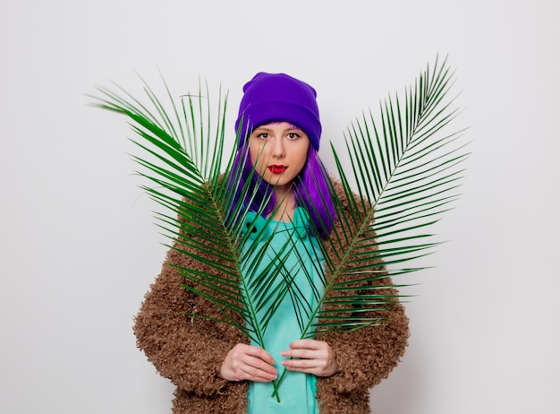Girl with purple hair in jacket with palm leaf