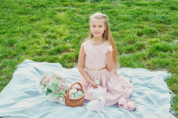 Girl with rabbit and eggs for easter in the park on green grass