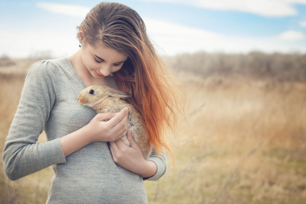 The girl with the rabbit.happy little girl holding cute fluffy bunny