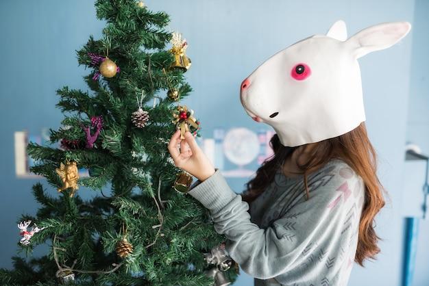 Girl with rabbit mask decorated xmas tree