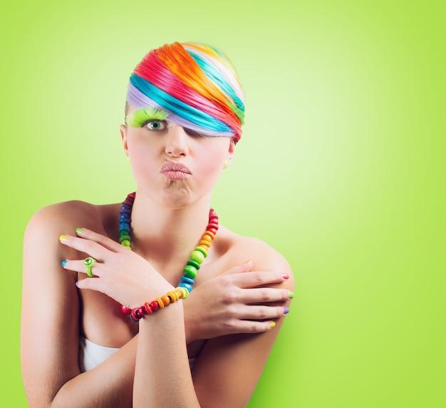 Девушка с радужным красочным модным макияжем на зеленом фоне.