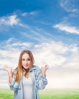 Girl with raised shoulders in a cloud background