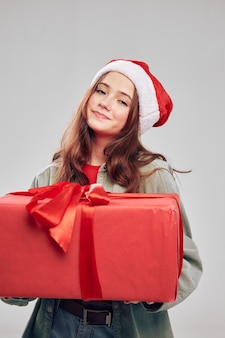 Девушка с красной коробкой и большим бантом шляпа санта-клауса рождество новый год. фото высокого качества