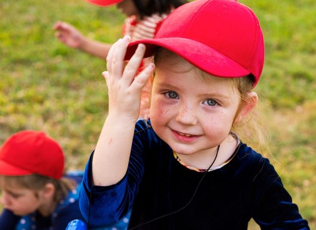 Girl with red cap is smiling to camera