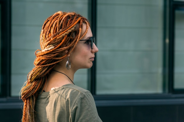 Девушка с красными дредами позирует на фоне офисного здания. вне. нестандартный внешний вид