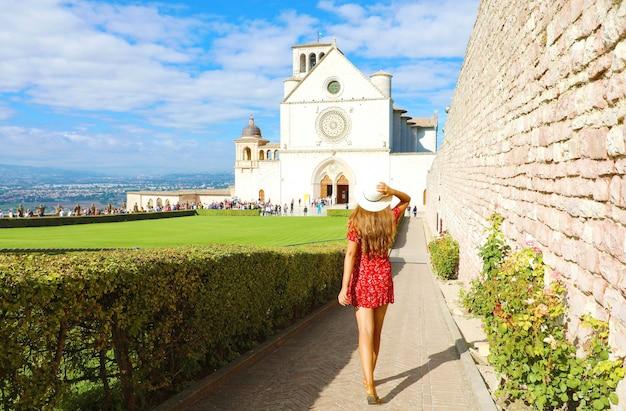 イタリア、ウンブリア州のアッシジ大聖堂と赤いドレスの女の子