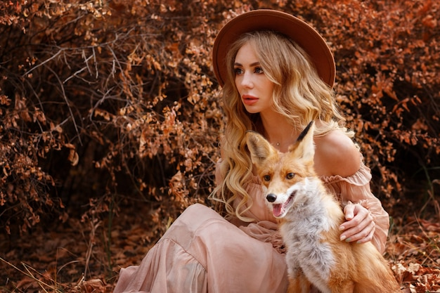 Девушка с рыжей лисой выглядывает осенью