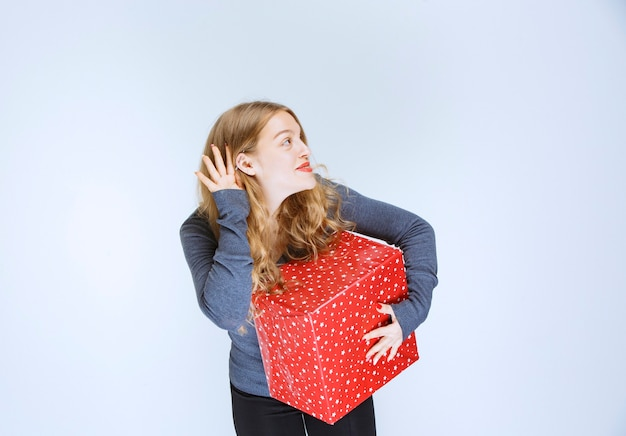 Ragazza con una confezione regalo rossa che apre l'orecchio e ascolta attentamente.