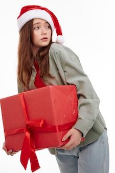 Девушка с красной подарочной коробке шляпа санты новый год рождество. фото высокого качества