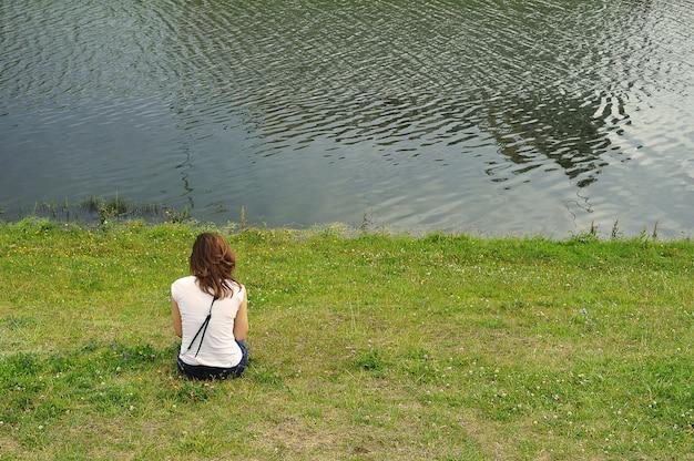 赤い髪の少女は湖のそばの緑の芝生に座っています-背面図