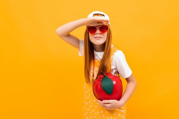 赤い髪のポーズと黄色に分離された小さなアップルバッグと笑顔の女の子