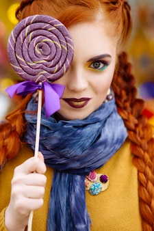 A girl with red hair walks and has fun in an amusement park, holding a lollipop in her hands.
