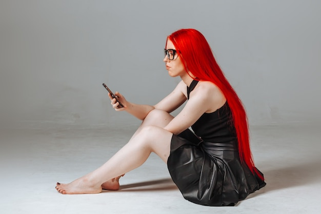 Girl with red hair wearing glasses and a leather skirt types message on the phone