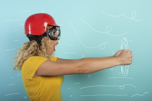 Девушка в красном шлеме думает водить быструю машину. голубая стена
