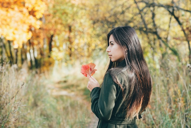 Girl with red leaf in autumn forest in sunrise.
