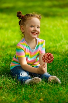 Девушка с красным леденцом на палочке сидит на летней траве в парке.