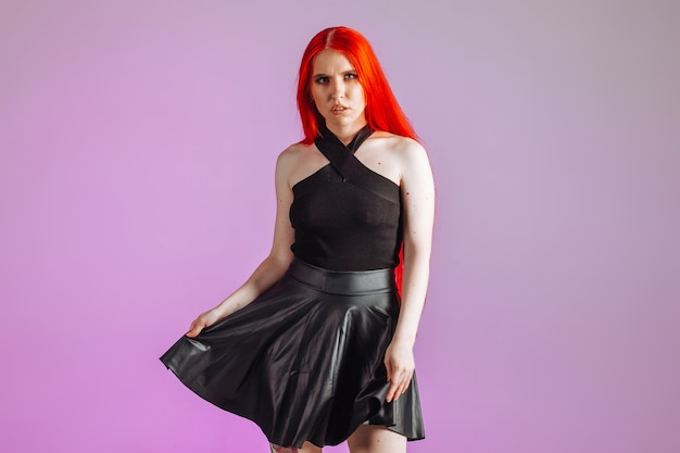 Girl with red long hair and leather skirt posing on pink background