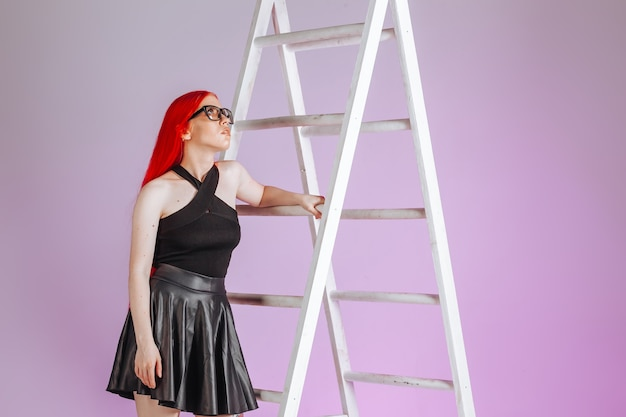 Girl with red long hair wearing glasses and a leather skirt climbs a ladder on a pink background