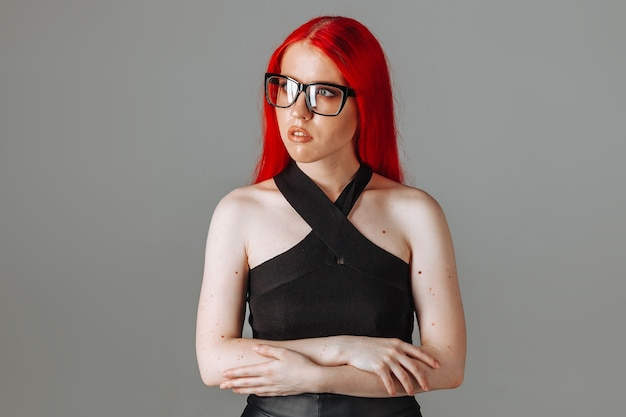 Girl with red long hair wearing glasses and a leather skirt posing on a gray background