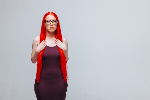 Girl with red long hair wearing glasses on a light gray background