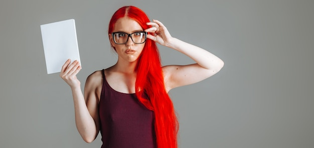 Girl with red long hair wearing glasses with a white book
