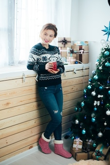 Girl with a red mug in her hands near the window on the background of a christmas tree