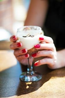 Девушка с красными ногтями держит кремовый десерт в стакане