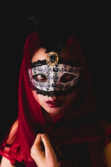 Girl with a red scarf on her head and a venetian mask