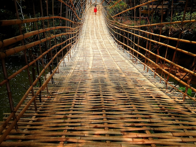 A girl with red suit walking on bamboo bridge