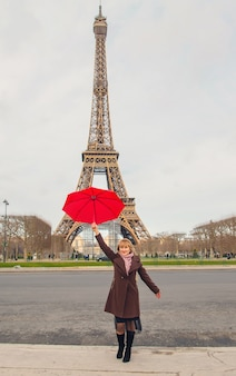 Girl with a red umbrella near the eiffel tower in paris. selective focus.