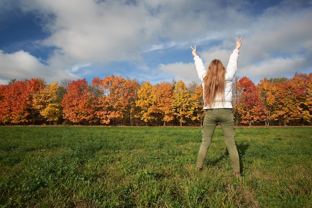 Girl with redhead natural long hair wearing white jacket and green pants showing sing victory. colorful autumn forest on background. autumn vibes. view from back.