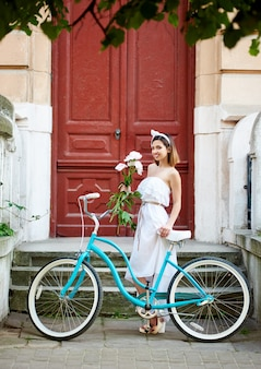 Girl with a retro bicycle and a bouquet of peonies