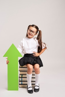Girl with rising arrow sitting on books
