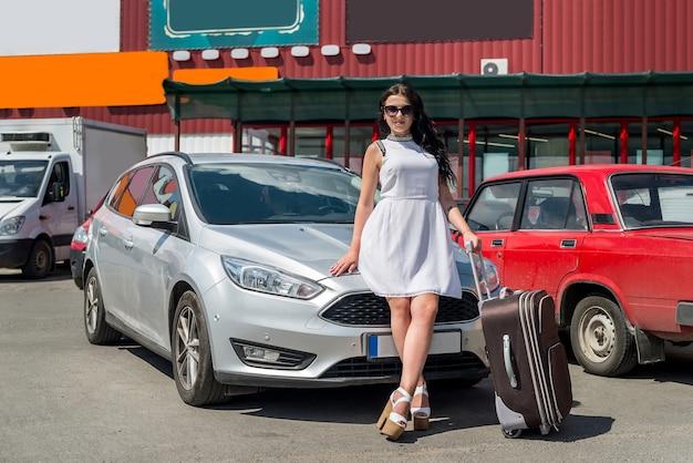 車の近くの道路のスーツケースを持つ少女