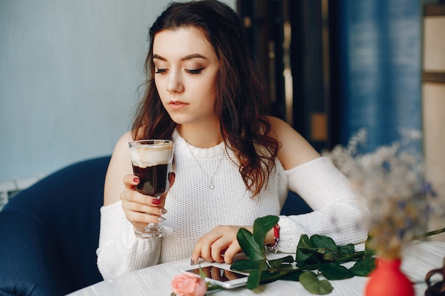 A girl with the rose and dessert in cafe