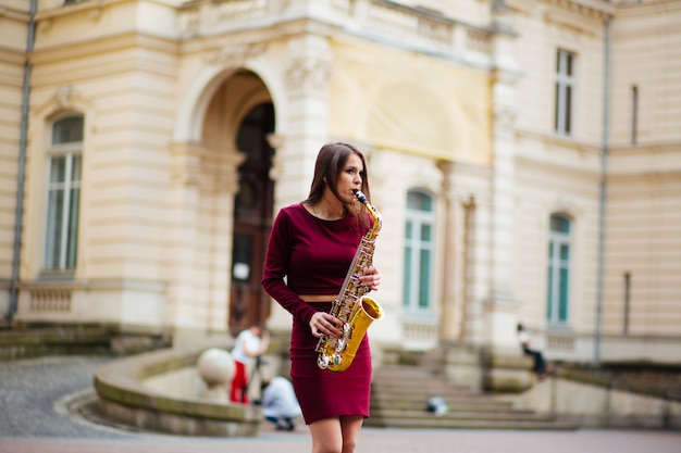 Девушка с саксофоном на улице