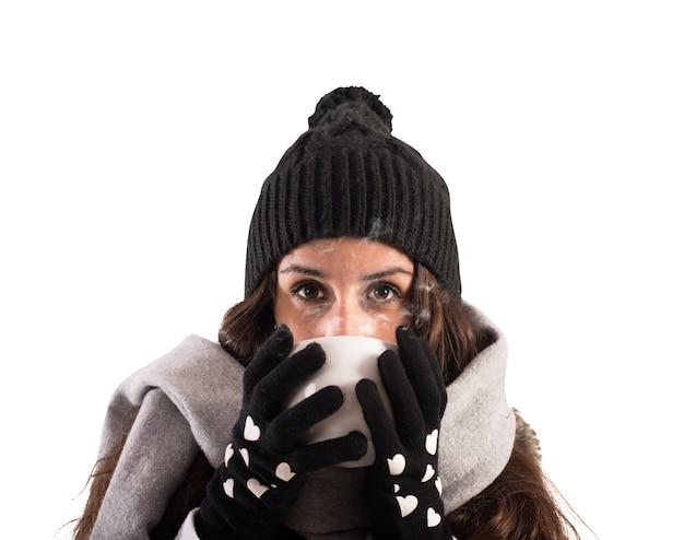 Девушка с шарфом и шерстяной шляпой пьет из чашки