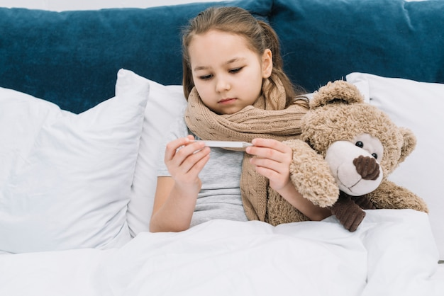 Girl with scarf around her neck sitting with teddy bear looking at thermometer