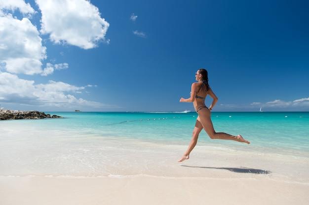 화창한 날 자연 환경에서 하얀 모래, 청록색 물, 푸른 하늘이 있는 바다 해변에서 수영복을 입은 섹시한 몸매를 가진 소녀. 선탠, 목욕. 여름 방학. 여유롭고 활동적인 레저