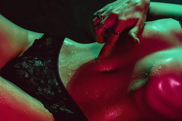 Girl with a sexy body touches her tummy with her hand next to her panties. female beautiful slender figure with drops of water and sweat on skin with neon lighting on dark background