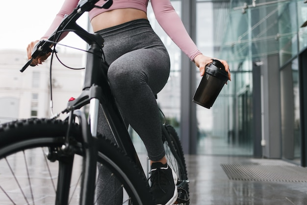 Girl with shaker in hand on a bicycle