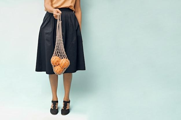 Девушка с хозяйственной сумкой апельсинов