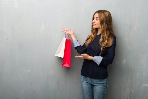 Girl with shopping bags extending hands to the side for inviting to come