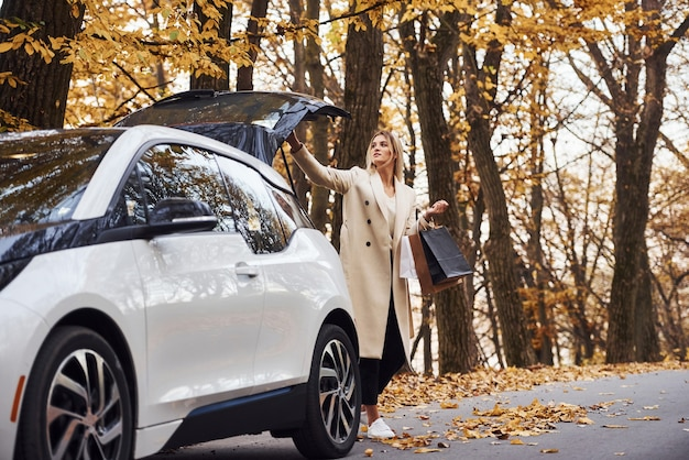 Girl with shopping bags in hands have autumn trip by car. modern brand new automobile in the forest.