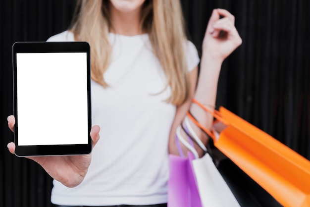 Girl with shopping bags holding tablet mock-up