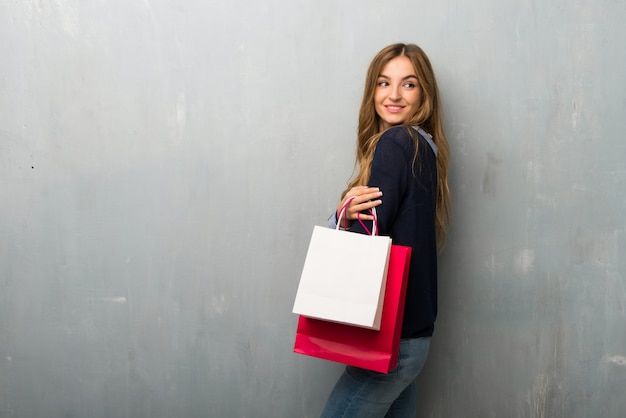 Girl with shopping bags looking over the shoulder with a smile
