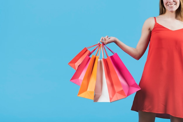 Girl with shopping bags on plain background