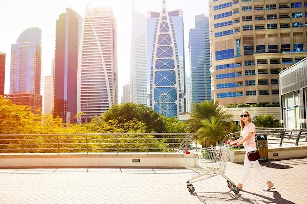 Девушка с покупками коляски гуляет по мосту перед небоскребами